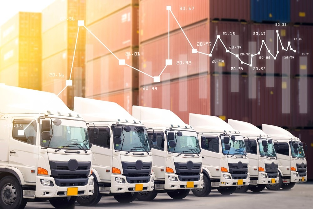 Image of multiple fully-electric trailer semi-trucks lined up in a row, with supply-chain logistics data in the background.
